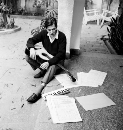 Tom-Jobim composing on the guitar with some paper notes spread on the floor