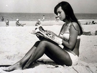 Helô Pinheiro the original girl from ipanema on the beach reading a magazine