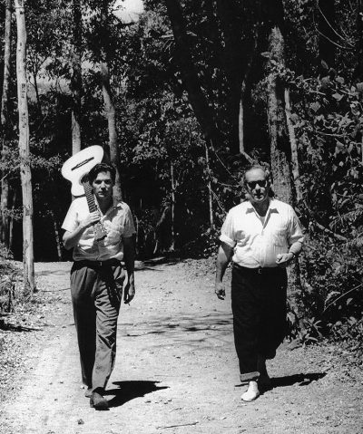 Carlos Jobim with Vinicius de Moraes walking on a garden