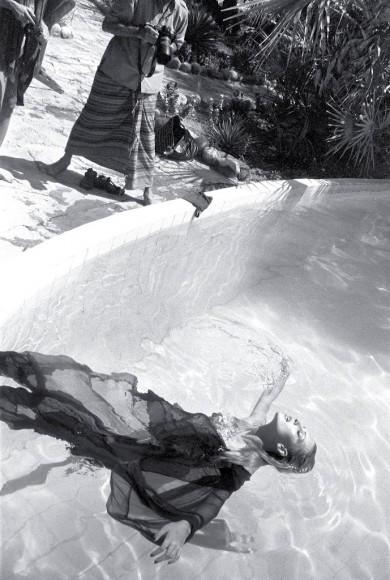 Peter Beard fashion shooting model floating on a pool