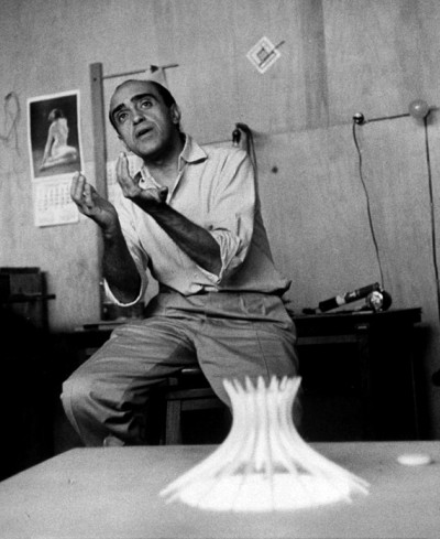 OSCAR NIEMEYER talking in his studio with a cathedral model