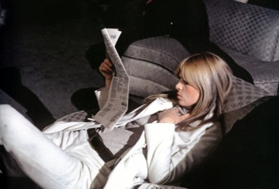nico in white suit reading a newspaper