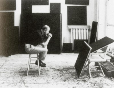 artist AD REINHARDT at work siting on a ladder studio new york