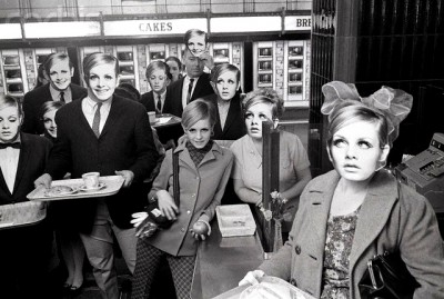 In an automat cafeteria, surrounded by regular people wearing masks of her face in New York.