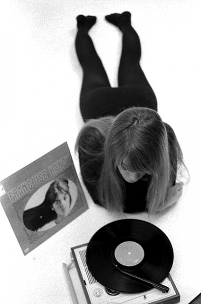 Fançoise Hardy on the floor listening to a portable record player