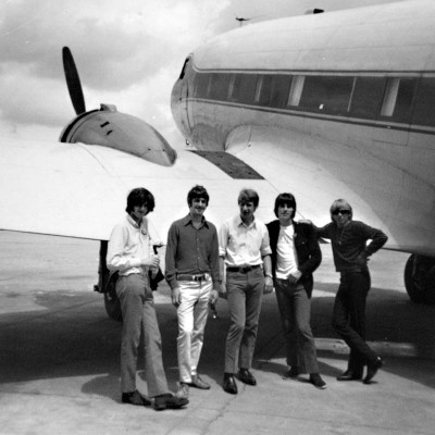 british rock band the yard birds posing next to an airplane
