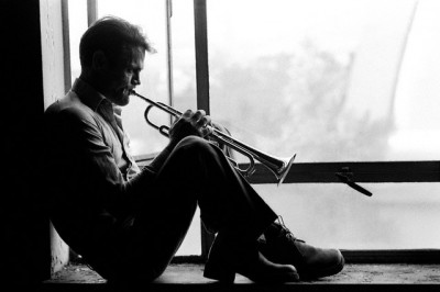 Chet Baker Playing Trumpet sintting on a window