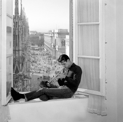 Chet baker in Milan playing trompet in a window cathedral background