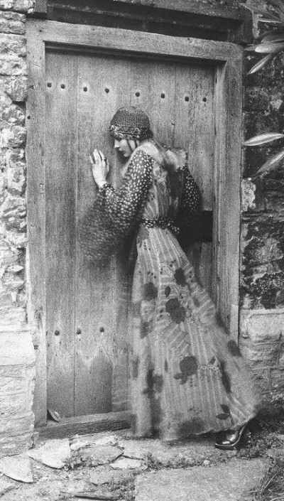 model in Ossie Clark leaning on a rustic door boho syle