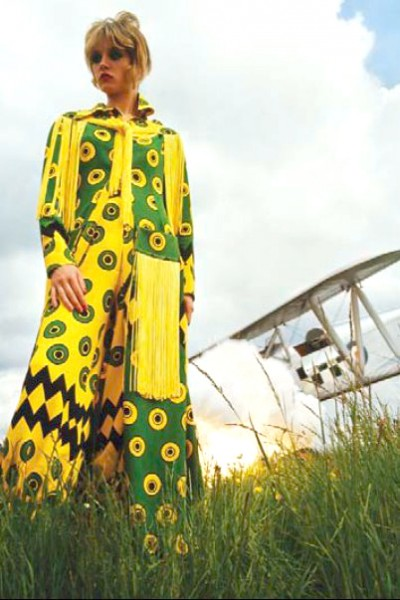 model in a designer Ossie Clark dress with airplane as a prop background