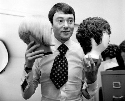 vidal sassoon showing 2 wigs in both hands