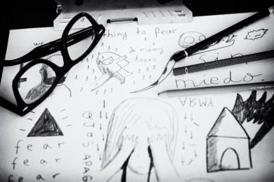 gafas sobre una mesa de dibujo con ilustraciones de Aitor Saraiba. Glasses on a drawing board with illustrations by Aitor Saraiba.
