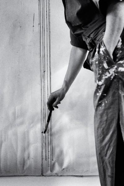 foto del estudio de la artista carmen la griega del fotografo Barte, artista pintando con brocha sobre un papel en la pared