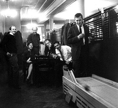 From left, American artists Bill Giles, Anna Moreska, and Robert Rauschenberg (1925 - 2008), with choreographer Merce Cunningham (1919 - 2009) and composer John Cage (1912 - 1992) (in white shirt), watch artist Jasper Johns play skee-ball in Dillon's Bar (80 University Place), New York, New York, November 10, 1959. (Photo by Fred W. McDarrah/Getty Images)