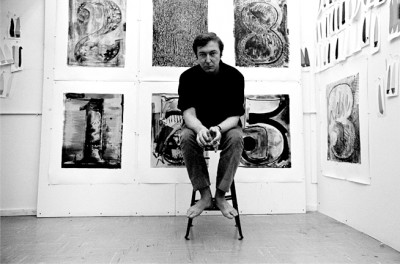 jasper johns posing on a stool in front of several of his artworks