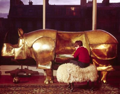 Large brass rhinoceros designed by Francois-Xavier Lalanne with folding sides being used as a desk by a little boy, also has a piggy-bank head with coin-drops in the ears --1967