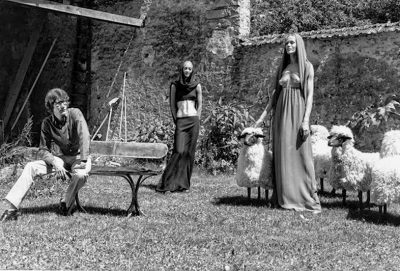Yves Saint Laurent in his garden with sheep by Les Lalanne and models wearing the Haute Couture A:W69 collection with sculpted busts and waists by Claude Lalanne