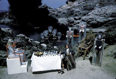 """Salvador DALI dîne avec la reine de Vénus dans la crique de Couliaro à CADAQUES : le peintre assis en face de Frédérika vêtue d'un scaphandre en S entourés de trois Vénusiens """"habillés"""" par Dali (plastique tendu sur un bâti de bois avec des ouvertures pour la tête, le mains et les pieds)"""